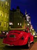 Véhicule rouge sur la rue de nuit Photographie stock libre de droits