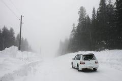Véhicule sur une route de l'hiver Photographie stock libre de droits