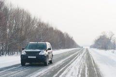 Véhicule sur une route de l'hiver Photos libres de droits