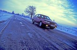Véhicule sur une route de l'hiver Image stock