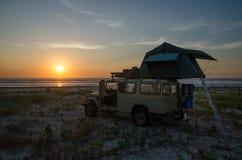 véhicule 4x4 tous terrains avec le camping de tente de dessus de toit sur la plage pendant le coucher du soleil, Casamance, Sénég Photographie stock