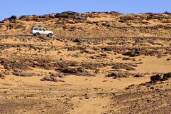 Véhicule tous terrains sur une route rugueuse de désert Images libres de droits