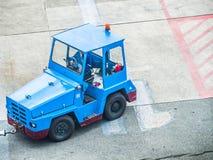 Véhicule tracteur bleu de bagage à l'aéroport Photographie stock libre de droits