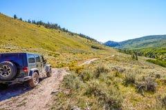 Véhicule 4WD chassant la route par des montagnes Photos libres de droits