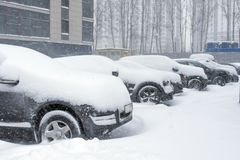 Véhicules couverts de neige dans la tempête de neige d'hiver dans le parking photo libre de droits