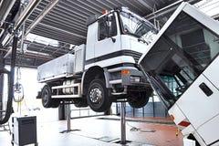Véhicules dans un garage - réparation et inspection des voitures sur un liftin photos libres de droits