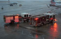 Véhicules de secours, ou camions de pompiers, sur le macadam à l'aéroport de lièvres de ` d'O Chicago par temps pluvieux Photos libres de droits