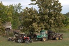 Véhicules de tracteur de ferme sous l'arbre à la maison de ferme de forêt Photos libres de droits