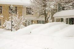 Véhicules et maisons dans la tempête de neige Image libre de droits
