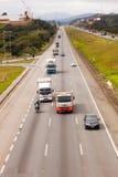 Véhicules sur la route BR-374 avec des phares dessus pendant la lumière du jour se conformant aux nouvelles lois brésiliennes de  photographie stock libre de droits
