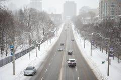 Véhicules sur la route détrempée par la neige Image stock