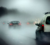 Véhicules sur une route en forte pluie et regain Image libre de droits