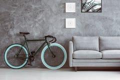 Vélo à côté de sofa gris photo libre de droits