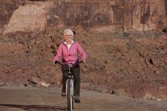 Vélo aîné d'équitation de femme par le désert Photos stock