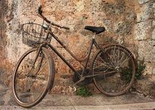 Vélo abandonné sur un mur Photos stock