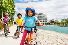 Vélo africain mignon d'équitation de fille en avant de ses amis Images libres de droits