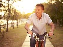 Vélo asiatique d'équitation d'homme dehors au coucher du soleil Photographie stock