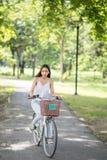 Vélo asiatique de tour de fille de brune en parc photographie stock libre de droits