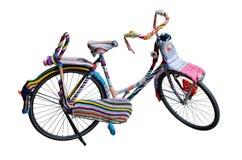 Vélo attaché avec les fils colorés de laine d'isolement sur le blanc Photographie stock