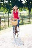 Vélo attrayant d'équitation de femme le long de ruelle de pays Photo libre de droits