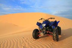 Vélo bleu de moteur à la dune de sable Images stock
