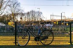 Vélo cassé verrouillé sur une barrière Image stock