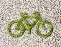 Vélo d'écologie d'herbe sur le fond criqué de la terre Images libres de droits