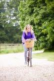 Vélo d'équitation d'adolescente le long de ruelle de pays Images stock