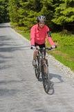 Vélo d'équitation de femme sur le chemin de recyclage ensoleillé Images stock