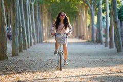 Vélo d'équitation de fille assez jeune dans une forêt Image stock