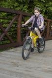 Vélo d'équitation de garçon sur la passerelle Image libre de droits