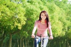 Vélo d'équitation de jeune femme et musique de écoute Images stock