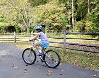 Vélo d'équitation de jeune fille photographie stock