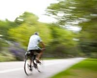 Vélo d'équitation sur le throug de lumière de matin le parc Image stock