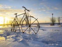 Vélo dans le coucher du soleil de neige photo stock