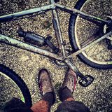 Vélo de montagne boueux avec les pieds boueux Images libres de droits