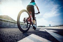 Vélo de montagne d'équitation de cycliste de femme photo libre de droits