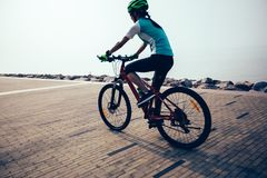 vélo de montagne d'équitation de cycliste sur le bord de la mer Photo libre de droits