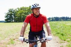 Vélo de montagne d'équitation d'homme le long de chemin dans la campagne Photo stock