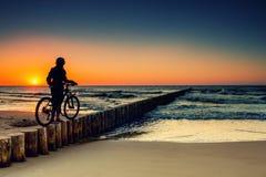 Vélo de montagne dans le coucher du soleil Photos stock