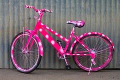Vélo de montagne de rose de mur de zinc Photographie stock libre de droits