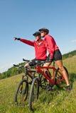 Vélo de montagne folâtre d'équitation de couples dans le pré Image libre de droits