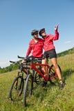 Vélo de montagne folâtre d'équitation de couples dans le pré Photo stock