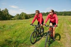 Vélo de montagne folâtre d'équitation de couples dans le pré Photos libres de droits