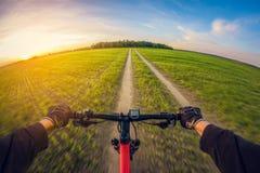 Vélo de monte sur le chemin de terre dans le domaine au coucher du soleil, vue de la première personne, lentille de fisheye de pe photographie stock