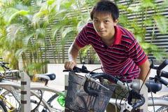 Vélo de prise d'homme de l'Asie en stationnement de bicyle Image libre de droits
