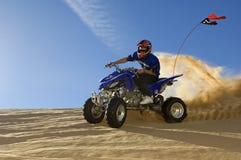 Vélo de quadruple d'équitation d'homme dans le désert photo stock