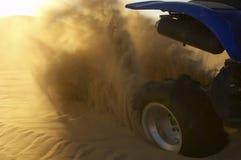 Vélo de quadruple pulvérisant vers le haut du sable Images stock