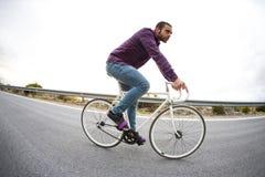 Vélo fixe de monte de sport de vitesse d'homme de cycliste dans le jour ensoleillé Photos stock