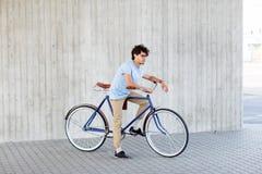 Vélo fixe de monte de vitesse de jeune homme de hippie photographie stock libre de droits
